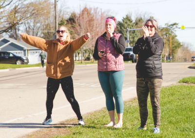 Three women cheering on their teammate on the side of the road